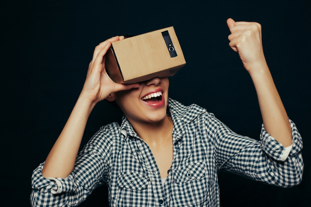 Color shot of a young woman looking through a cardboard, a device with which one can experience virtual reality on a mobile phone. girl touches a hand, finger virtual world.